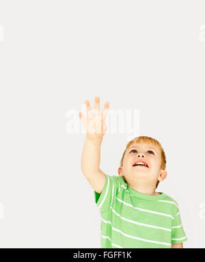 Boy reaching his hand out into the sky - Stock Photo
