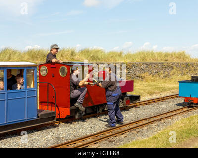 Two steam engine drivers of a narrow gauge seaside railway exchange tokens to allow safe for the next section of - Stock Photo