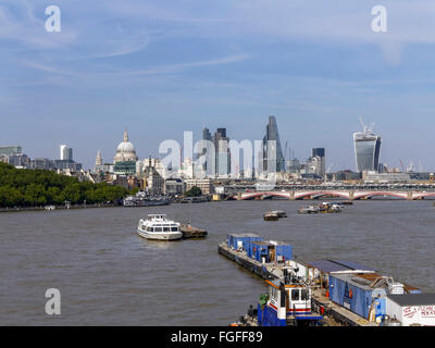View looking down the river Thames from Waterloo bridge with busy river work and busy London city skyline and river - Stock Photo