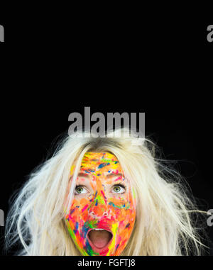 Woman with messy blonde hair and face covered in multi coloured paint with a surprised expression - Stock Photo