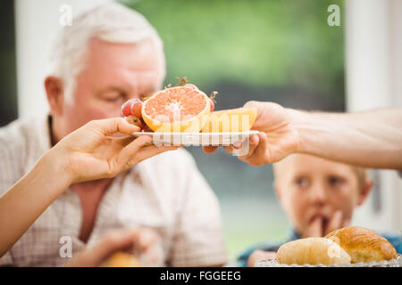 Close-up of hands passing plate of fruits - Stock Photo