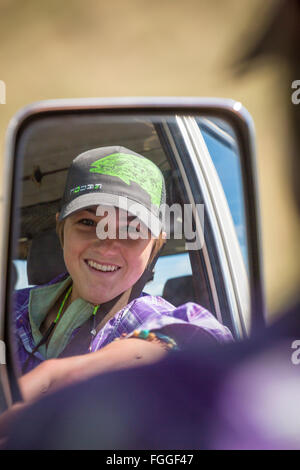 A young woman reflects in the side mirror of a 1990 Toyota Land Cruiser. - Stock Photo