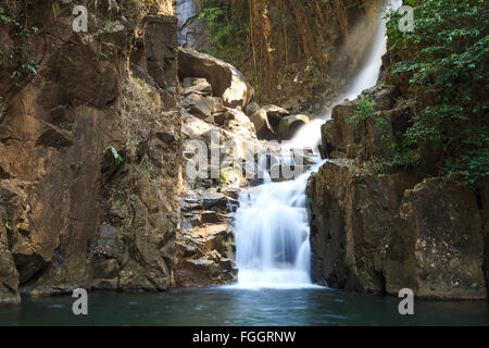Soft waterfall with dark brown rock of Phlio National Park at Chanthaburi in Thailand. In this pool has many black - Stock Photo