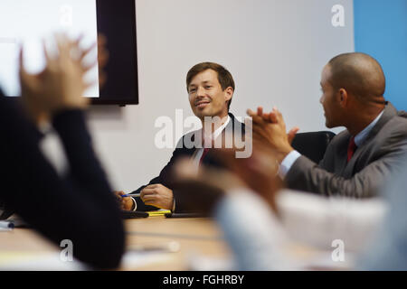Group of business people meeting in corporate conference room, applauding at a coworker during his presentation. - Stock Photo