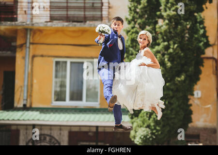 couple jumping on the street - Stock Photo