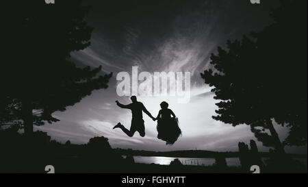 groom and bride jumping against the beautiful sky - Stock Photo