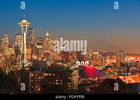 Seatlle skyline after sunset at twilight on a cold early winter evening with beautiful snow coverred Mount Rainier - Stock Photo
