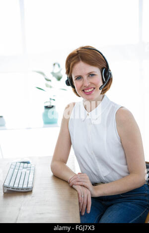smiling hipster business woman wearing a headset - Stock Photo