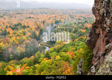 Porcupine Mountains Carp River Valley. Autumn colors pop with saturation from the mist as fog drifts above the river. - Stock Photo