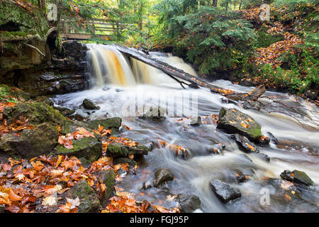 Autumn leaves are strewn along riverbanks and on rocks as Upper Chapel Falls cascades downriver at Pictured Rocks - Stock Photo