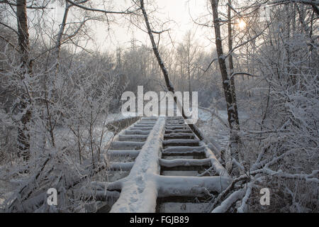 Old broken wooden pedestrian bridge covered with snow in winter