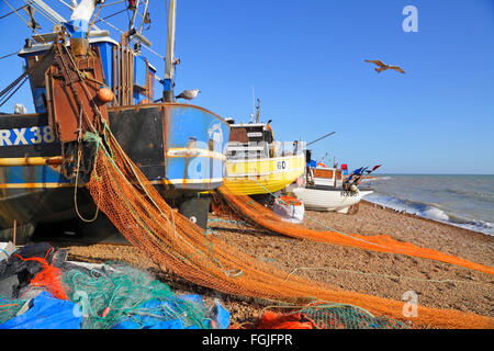 Hastings UK. Fishing boats with colourful nets drying on the Stade fishermen's beach, East Sussex, England, GB - Stock Photo