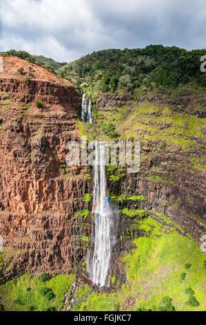 Aerial view of a cascading waterfall and its rainbow, Kauai, Hawaii. - Stock Photo