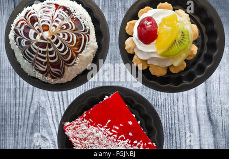 Cakes in tins on the old Board. - Stock Photo