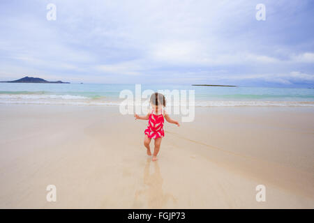 One year old girl playing in the waves in her swimsuit at Kailua Bay Beach in Oahu Hawaii. - Stock Photo
