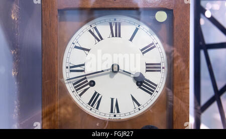 Antique wind up clock with roman numerals on its face inside glass case at museum - Stock Photo