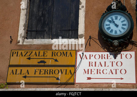 Confusing Street Signs on a wall in Venice, Italy - Stock Photo