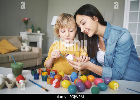 Young woman and her cute son painting Easter eggs together before holiday - Stock Photo