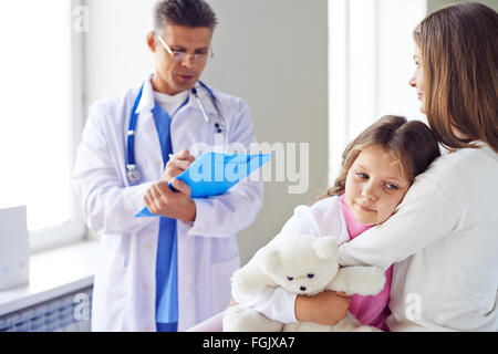 Cute girl embracing her mother in hospital during visit to doctor - Stock Photo
