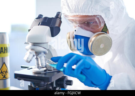 Modern chemist in protective clothing analyzing characteristics of toxic fluid in laboratory - Stock Photo