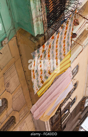 Daily life in Cuba - Cuban women looking down over washing hung out to dry on balcony at Havana, Cuba, West Indies, - Stock Photo