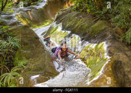 Child on water slide in the forest, smiling and enjoying - Stock Photo