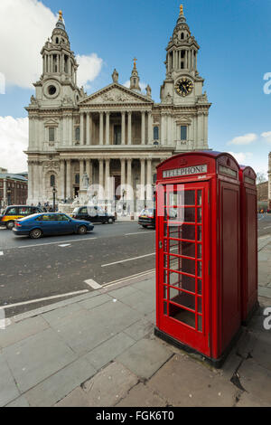 Red phone box in front of St Paul's Cathedral in London, UK. - Stock Photo