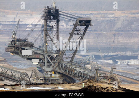 Digger machine in a brown coal open pit mine - Stock Photo
