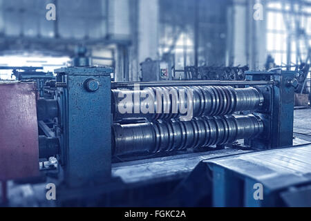 machine for slitting steel sheet. Toned image with tilt-shift effect. - Stock Photo