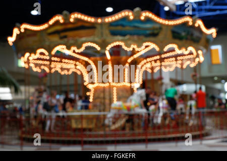 A magical out of focus carousel or merry go round - Stock Photo