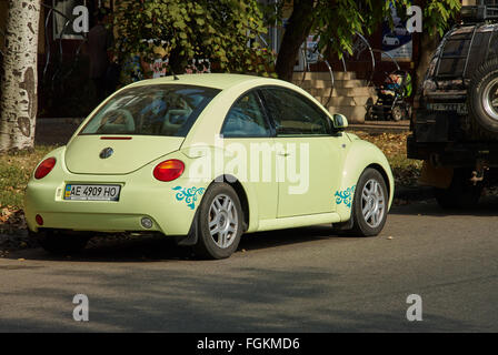 Krivoy Rog, Ukraine - September 24, 2015: Light green Volkswagen New Beetle car parked in a street of the city centre. - Stock Photo
