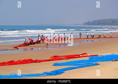 Fishermen hauling nets in on a beach in Maharashtra, South India - Stock Photo
