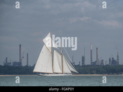 a classic yacht with two masts in full white sail sails past Fawley Power Station on a sunny day on The Solent, - Stock Photo