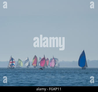 a group of yachts racing with full colorful colourful spinnakers on calm water under a large clear blue Solent sky, - Stock Photo