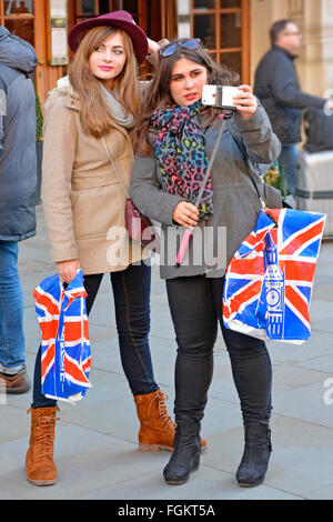 Young women each holding union jack shopping bag preparing to use a selfie stick & apple phone whilst shopping in - Stock Photo