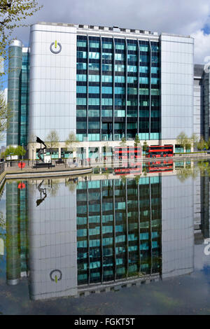 Premises of Global Switch data centre provider & reflections in landscaped water feature note bus adverts digitally - Stock Photo