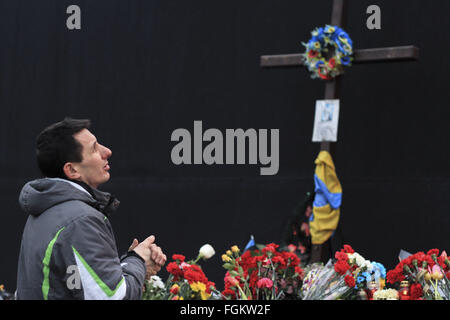 Kiev, Ukraine. 20th Feb, 2016. Ukrainian man prays during a visit at a temporary memorial for Revoluton of Dignity - Stock Photo