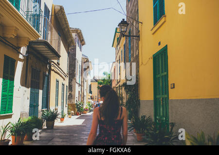 Back view of young woman walking on spanish streets - Stock Photo