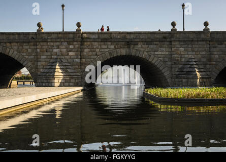 Vision from far of a fountain under the bridge of Manzanares river, Madrid city, Spain - Stock Photo