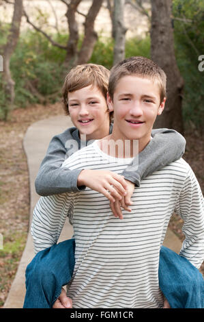 Two cute boys that are brothers riding piggy back on sidewalk smiling at camera. - Stock Photo