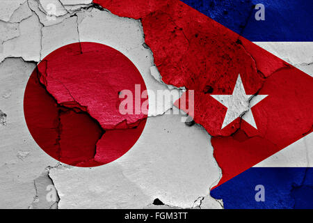 flags of Japan and Cuba painted on cracked wall - Stock Photo
