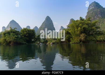 People taking bamboo raft along Yulong River, Yangshuo, Guangxi, China - Stock Photo