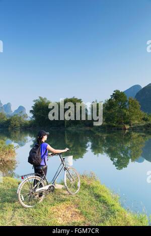 Woman cyclist on Yulong River, Yangshuo, Guangxi, China - Stock Photo