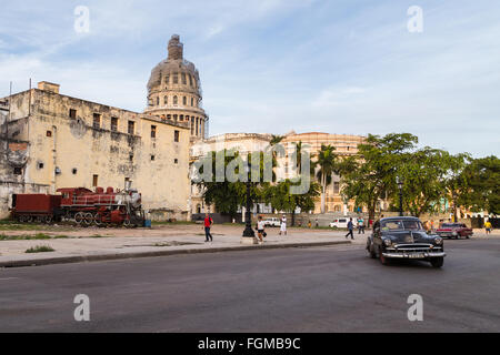 A row of trees, a road of old cars & an old steam locomotive seen in front of the Capitol Building in Havana. - Stock Photo
