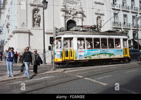 Portugal, Lisbon, city life, people crossing Largo Chiado street, vintage tram in front of Church Igreja do Loreto - Stock Photo