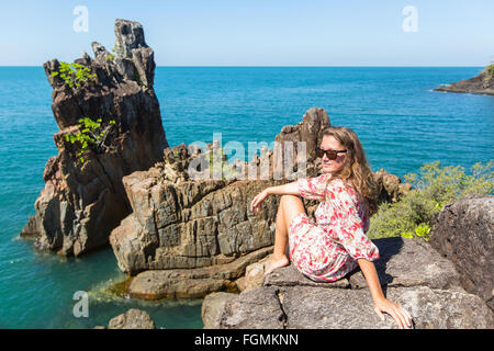 Young woman sitting on coastal rocks of Koh Chang island in Thailand. - Stock Photo
