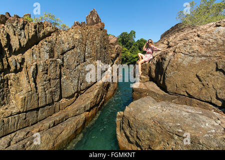 Beautiful woman sitting on coastal rocks of Koh Chang island in Thailand. - Stock Photo