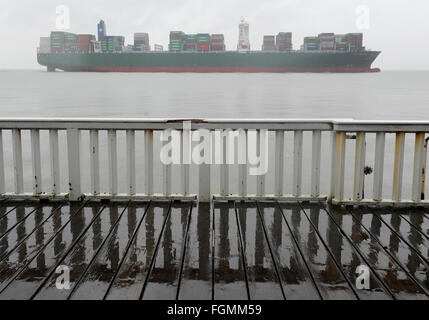 Cuxhaven, Germany. 21st Feb, 2016. Giant container vessel 'Thalassa Doxa' passes by the 'Alte Liebe' jetty in Cuxhaven, - Stock Photo