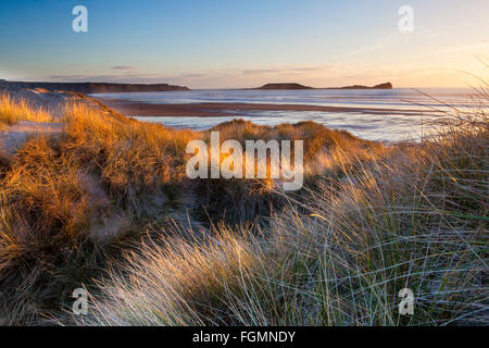 Sunset over Worms Head and Rhossili beach viewed from the sand dunes of Llangennith - Stock Photo