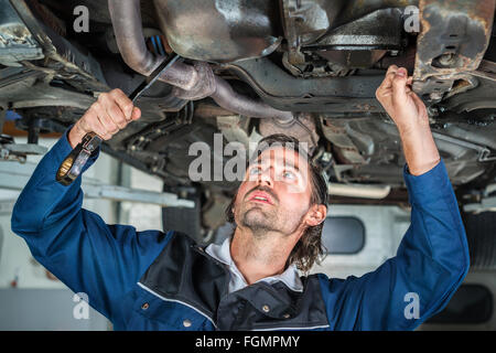 Mechanic repairing a lifted car wit - Stock Photo